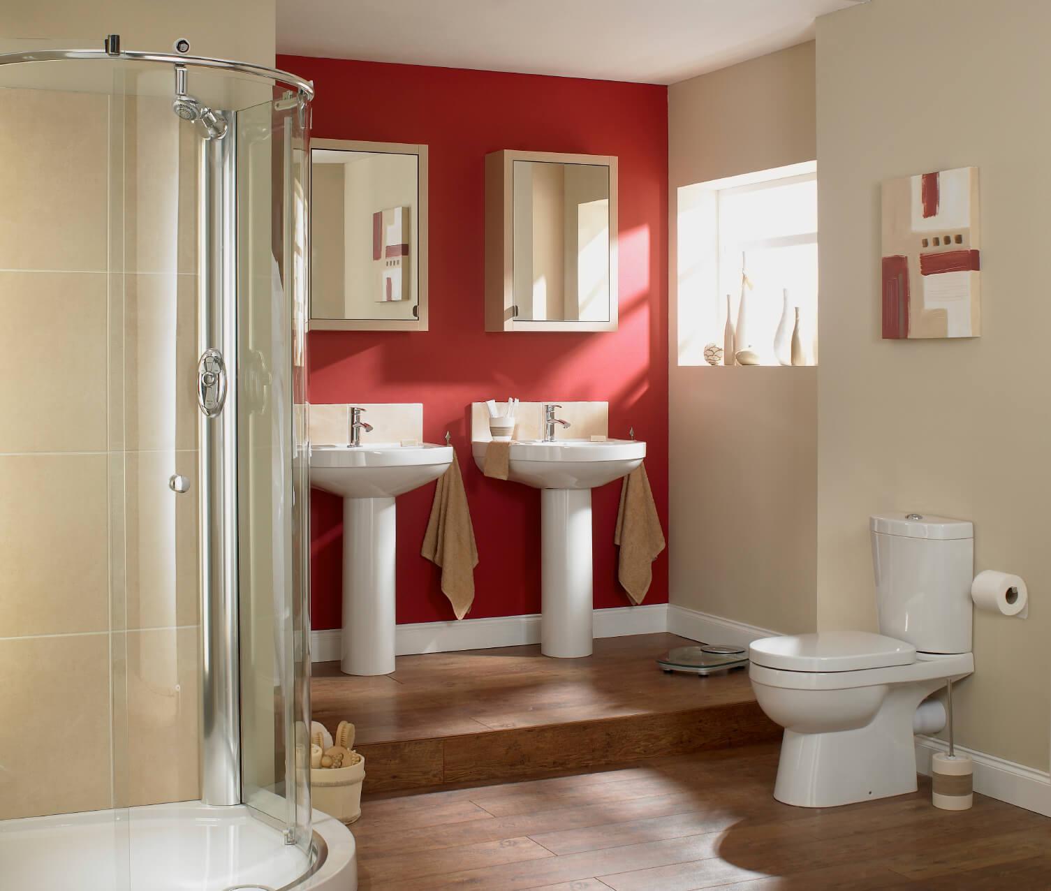 Salle de bain principale avec un mur rouge et un plancher de bois franc.  Il comprend également deux lavabos sur pied et une salle de douche ouverte.