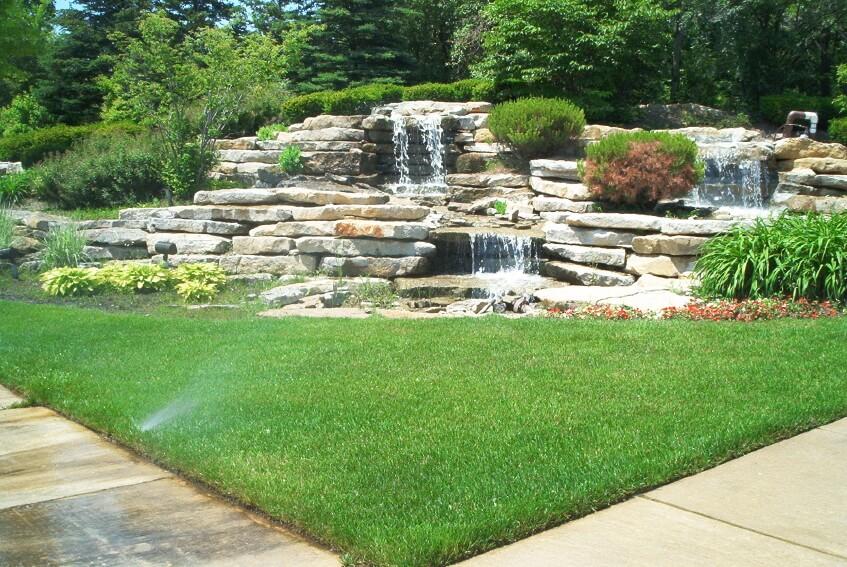 Layered stone waterfall in a corner of a backyard.