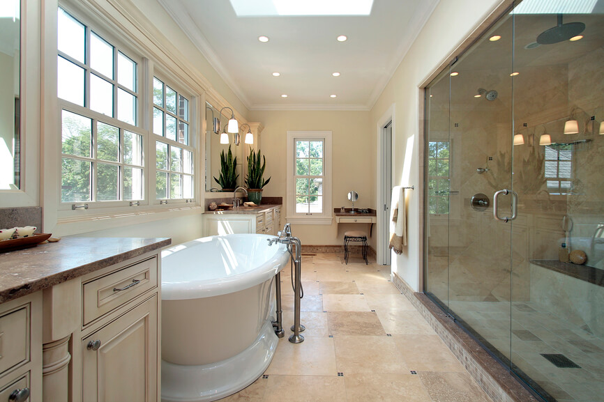 This impressive bathroom offers plenty of space. A deep porcelain bathtub boasts stainless steel spigots and plumbing, while a sizable glass enclosed shower is nearby. Recessed lighting is inset onto the crown moulded white ceiling, and a skylight complements the numerous windows already allowing for light to trickle through. Stone floor tile-work complements the soft neutrals of the walls and double vanities perfectly.