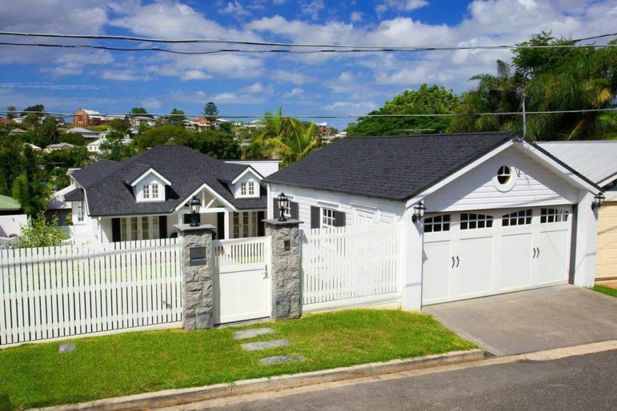 An aerial view from the street. A tall privacy fence with a gate closes off this home from the much higher street on the hill. The garage is separate from the main home, with a short driveway.