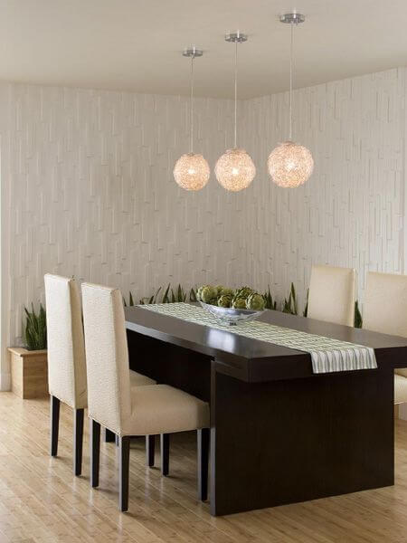 The main floor dining room has light hardwood flooring and a rich dark dining table with seating for four. A wooden planting box sits against the back wall in the same finish as the flooring. The walls are heavily textured and provide unique visual interest and contrast.