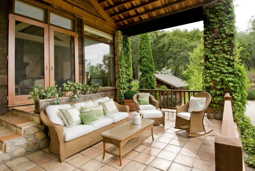 Stone and tile steps lead down from screened French doors to a lower tile patio looking out on a man made lake. Thick ivy climbs up the stone support columns of the roof for a whimsical effect. The furniture consists of a wicker sofa, armchair, ottoman, coffee table, and a rocking chair. Wooden railings surround and enclose this elevated deck and patio.