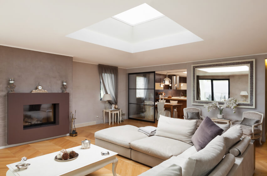 The same living room is featured from a different angle, revealing the chic mantel and elegant furnishing. The skylight is the only light source on the ceiling of this modern room.