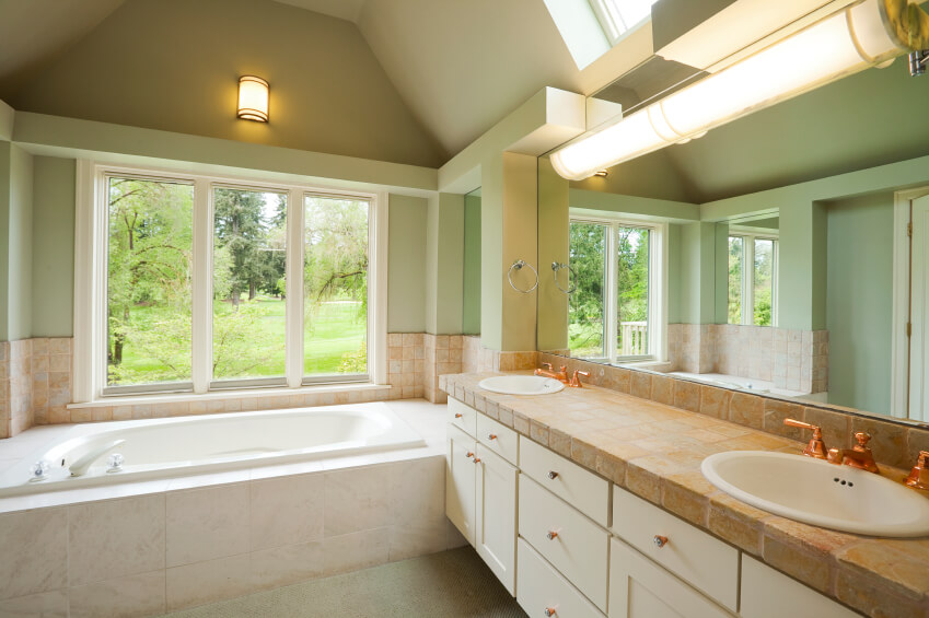 This charming bathroom is rich in ivory, beiges, and mint hues. The stone countertops of the double vanity offer an aesthetically pleasing option with gorgeous texture. Lighting fixtures look down upon the space offering the soft glow of conventional lighting, while a large window and skylight combine to brighten the area.