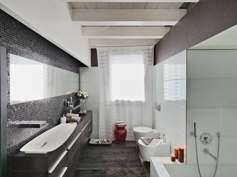 Salle de bain principale contemporaine avec un grand évier élégant sur le comptoir noir assorti au tapis recouvrant le plancher de bois franc.