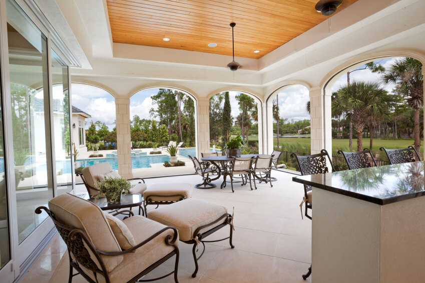 This massive covered stone tile patio features a small bar in addition to the cozy lounge chairs and a dining area nearer to the archways by the pool.