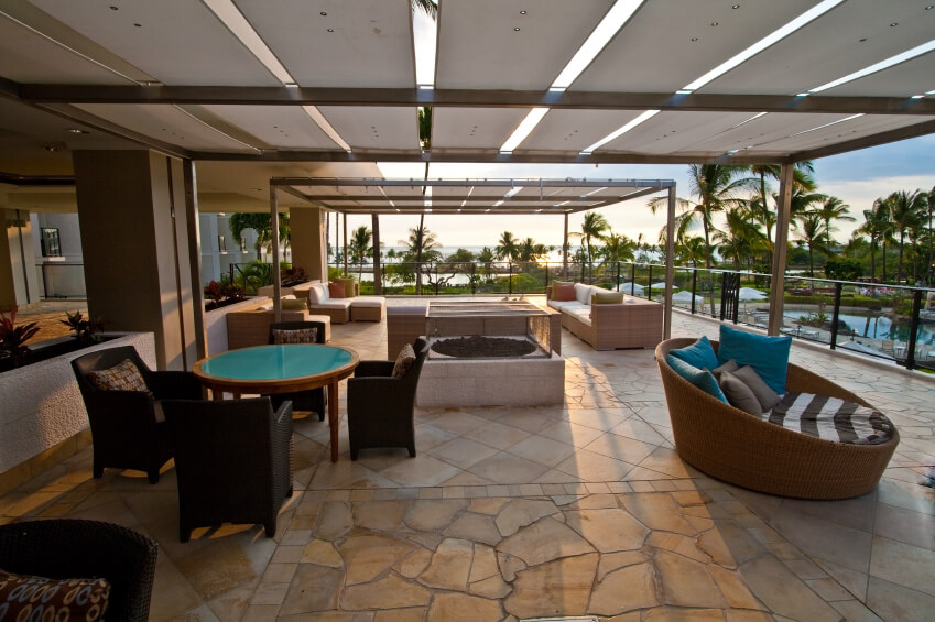 This stone tile patio features a number of different seating options, including a circular lounge chair and dark armchairs. This patio stretches the length of the building, tucked under panels. Sunlight filters through small gaps between the panels.