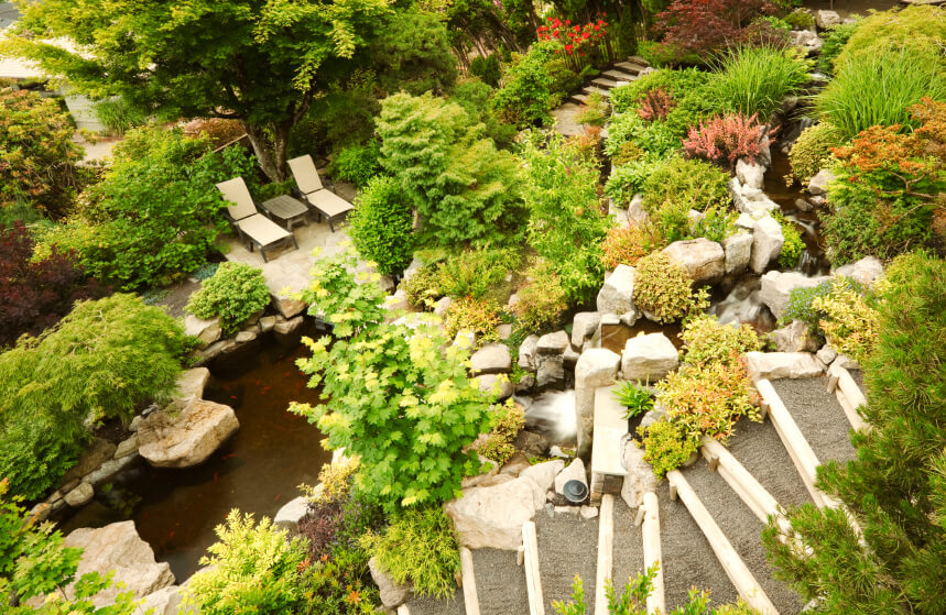 A bird's eye view of stone steps leading down past a stream with multiple waterfalls that ends in a pool surrounded by rocky outcroppings. A small patio with two lounge chairs is tucked into the forest-like garden.