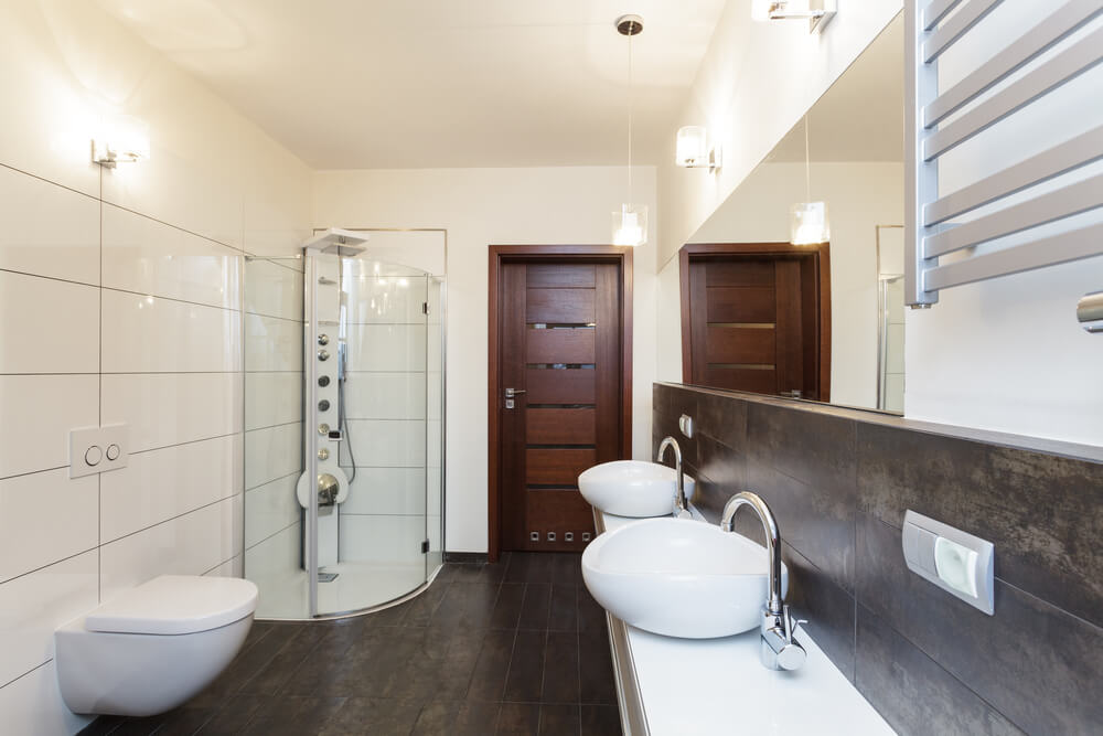 Une salle de bain principale avec des murs beiges et des planchers de bois franc.  Il dispose également d'une salle de douche à l'italienne et de quelques lavabos.