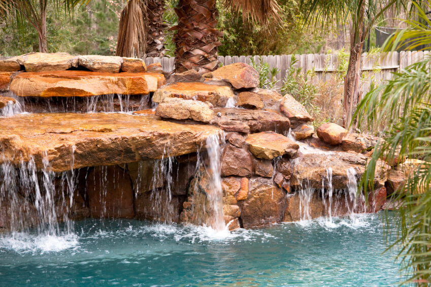 A natural stone stacked waterfall with water running off nearly every surface and into the pool.