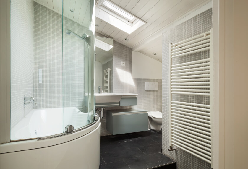 A modern industrial style bathroom features a rounded bathing area, heated towel rack, and petite gray tiles complementing the charcoal stone tiling of the floor. A skylight beams down from the angled planked ceiling, and a modern tankless toilet and sink round out this appealing bathroom.