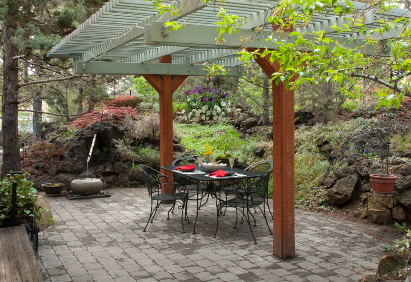 This Japanese Zen garden has a fusion of more western elements, including the wrought iron dining set tucked beneath the green pergola. A traditional bamboo and stone vessel fountain provides an atmosphere of tranquility.