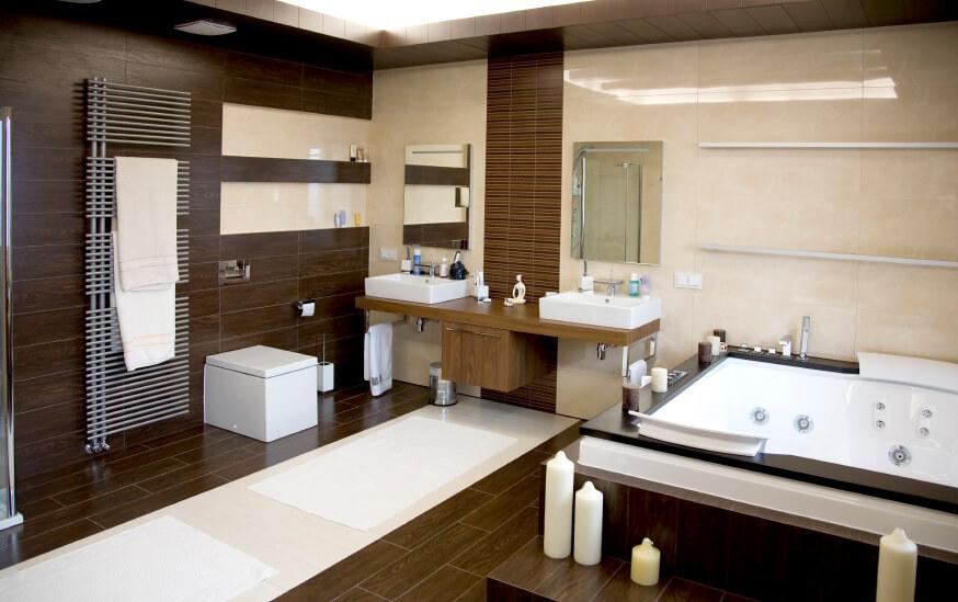 Salle de bain principale spacieuse avec une paire de lavabos et une grande baignoire encastrée, ainsi que des planchers et des murs en bois franc.