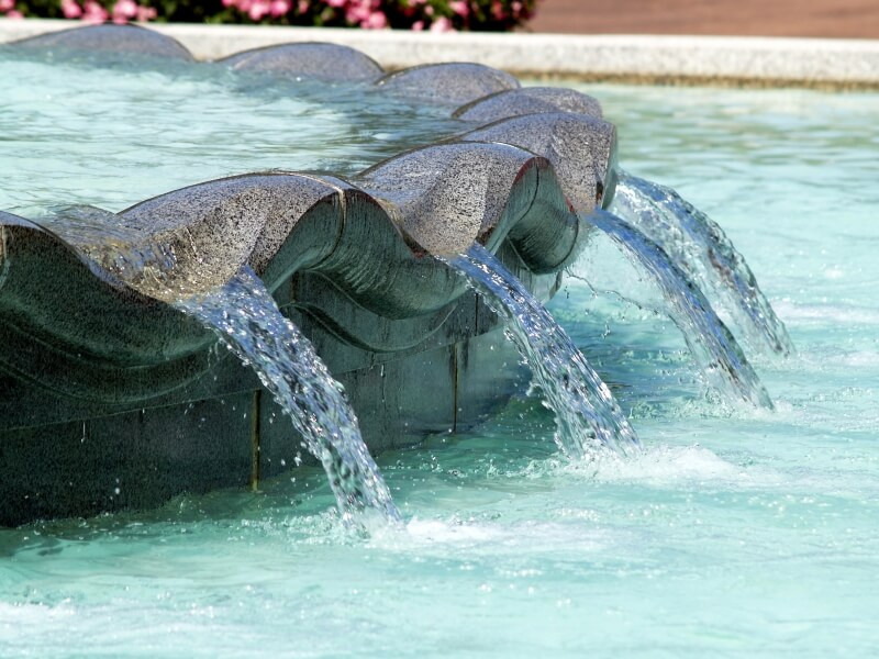 A water feature in the center of a pool with scalloped edges where the water flows back into the main pool.