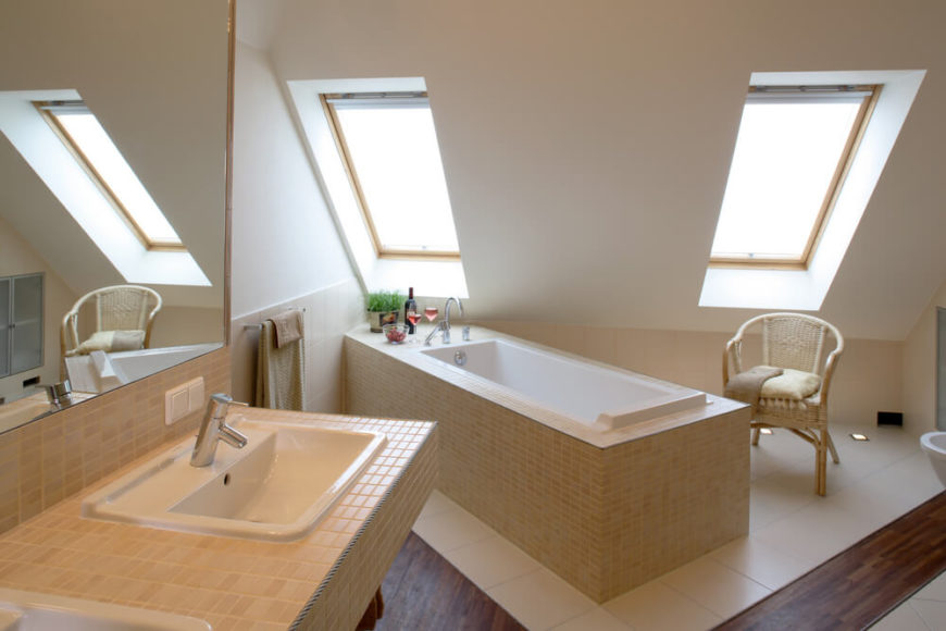 Double skylights filter light upon the finely tiled narrow bathtub. Glasses of wine are already prepared for a long relaxing soak, while the matching double vanity offers ample space. Large white ceramic tiles protect the hardwood floor from water damage, and a simple natural wood chair is on hand for comfortable bath preparations.