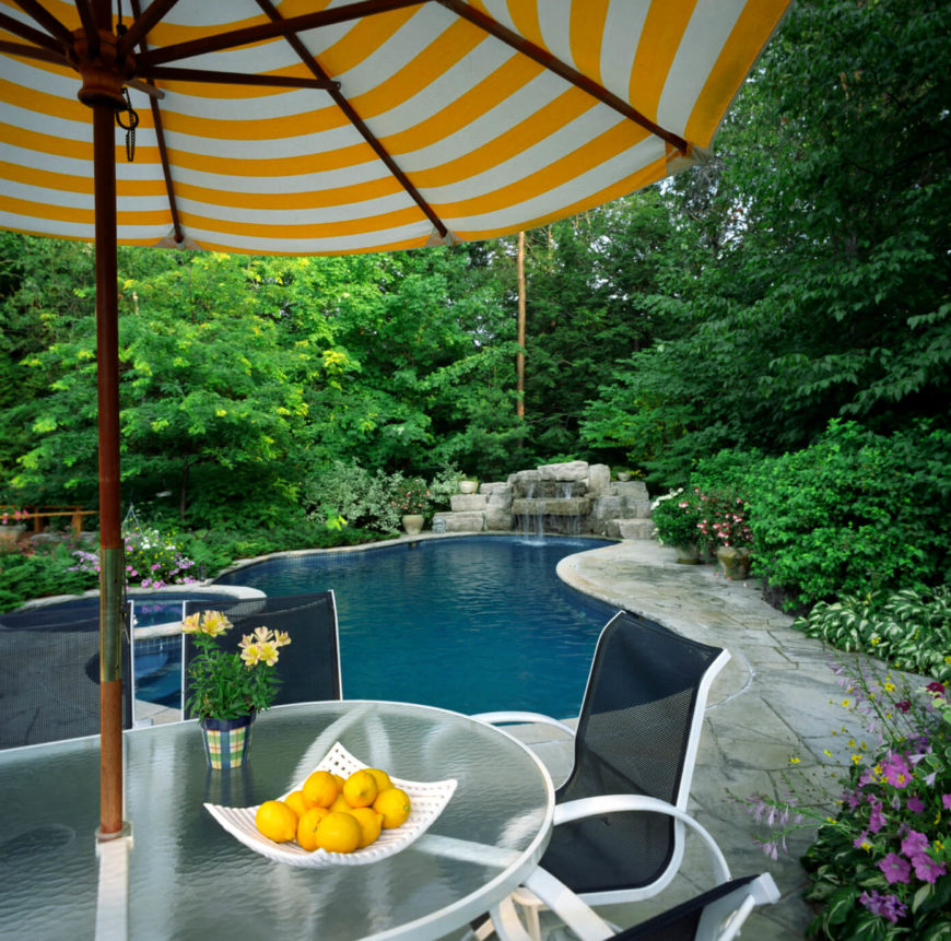 A backyard patio surrounded by lush landscaping with a pool and jacuzzi. A stacked stone waterfall runs into the pool and creates a lovely ambient sound.