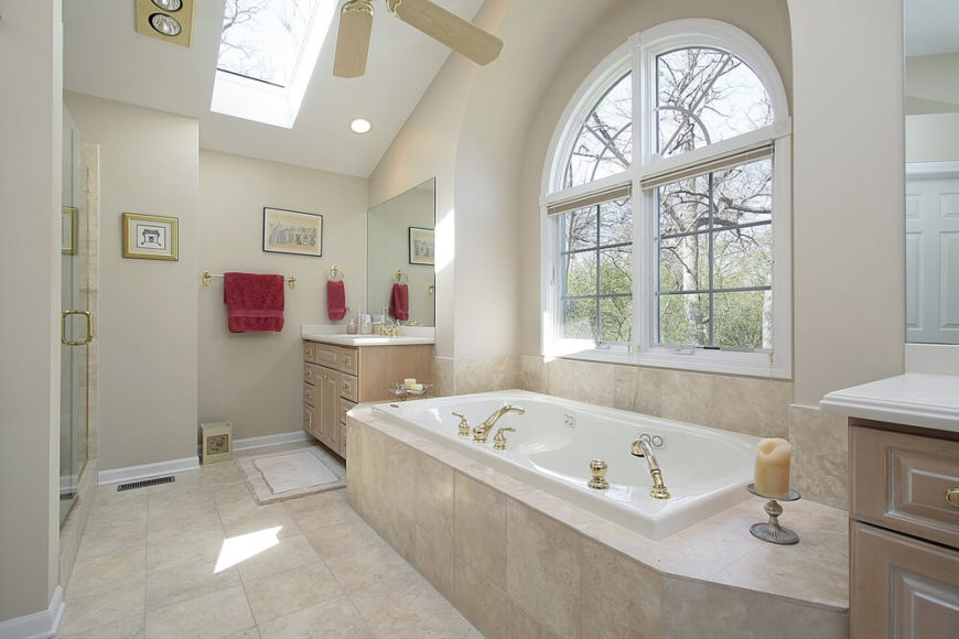 This neutral palette bathroom features stone tile-work, two vanities, and a lovely arched window allowing views of the outside world. A ceiling skylight allows for additional light flow in this already bright space, while maroon accent towels contribute vibrant color to an otherwise muted space.