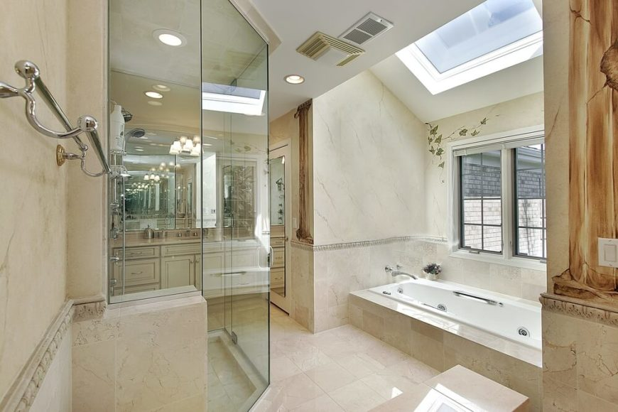 The above bathroom is elegantly designed in a cream and ivory palette. The light, glossy, stone tiled floor pairs nicely with the deeper hues of the surrounding tiled walls and bathtub encasement. A delicate spray of ivory is hand painted on the wall, as are textured faux pillars which add a classical sense of style to this space. A window above the bathtub allows a relaxing view of the outdoors, while a skylight allows rays of light to playfully bounce around the room.
