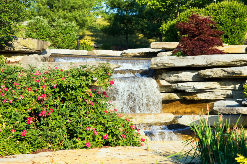 This garden waterfall has a small ledge of rock extending like a miniature bridge over one of the falls.