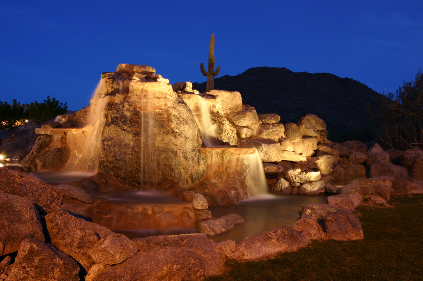 A fantastic water feature with multiple cascading pools, arranged from natural rock. Lights hidden within the stone alcoves create a stunning nighttime display.