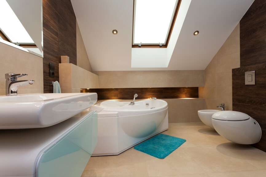 This wonderfully modern bathroom relies on an attractive skylight and recessed lighting to brighten the space. The gentle curves of the bathtub, sink, and bidet are eye catching and attractive. A lone turquoise bathmat offers a welcome splash of bold color against the neutral base of the cream tile flooring.