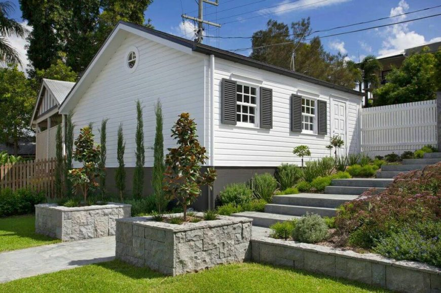 A series of stone steps lead down to the front yard from the street, passing the garage. Hardy shrubs and plants line the steps. At the bottom are matching ornamental trees in raised stone planters, which give the entryway a grand, polished look.