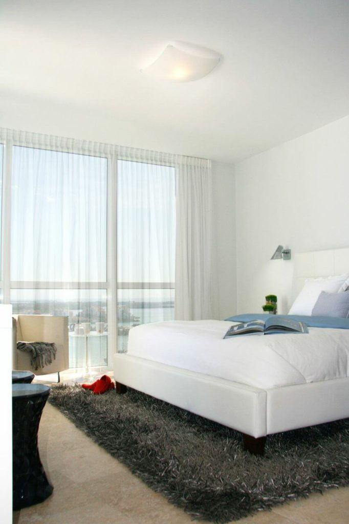 The third bedroom is also white, with the same tile as in the all-white bedroom. However, the white bedding and walls are paired with blue accents and a dark rug to create a more masculine room. Simple modern sconces beside the bed enhance that appearance.