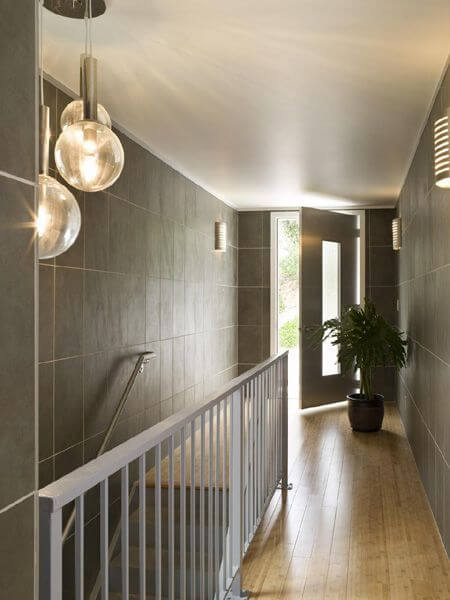 The upstairs hallway has delicate orb lighting, a stainless steel bannister, and a doorway leading outside.