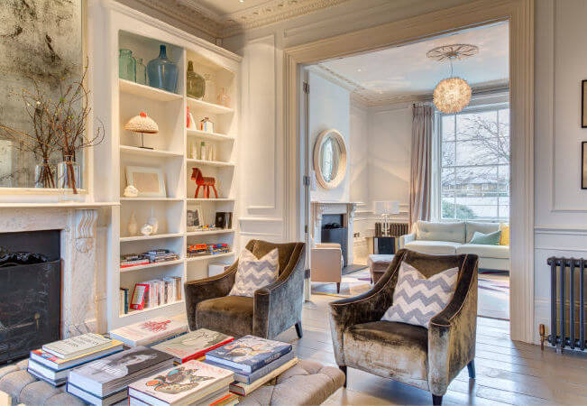 The home has three living room areas. Pictured in the foreground is a library and seating area, with a beautiful fireplace and built-in bookcases. Through the wide archway rimmed by crown molding is another living room, a more formal room with additional seating and an expansive window that looks out on the front yard.