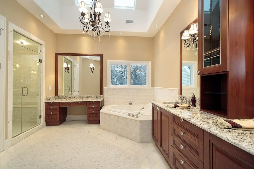 This luxury bathroom features rich wood cabinetry topped with fine marble. The light tile flooring coordinates with tile encasing the bathtub, while the darker walls offer a subtle contrast. Two skylights join an opulent chandelier, while a glass enclosed shower stands to the side.
