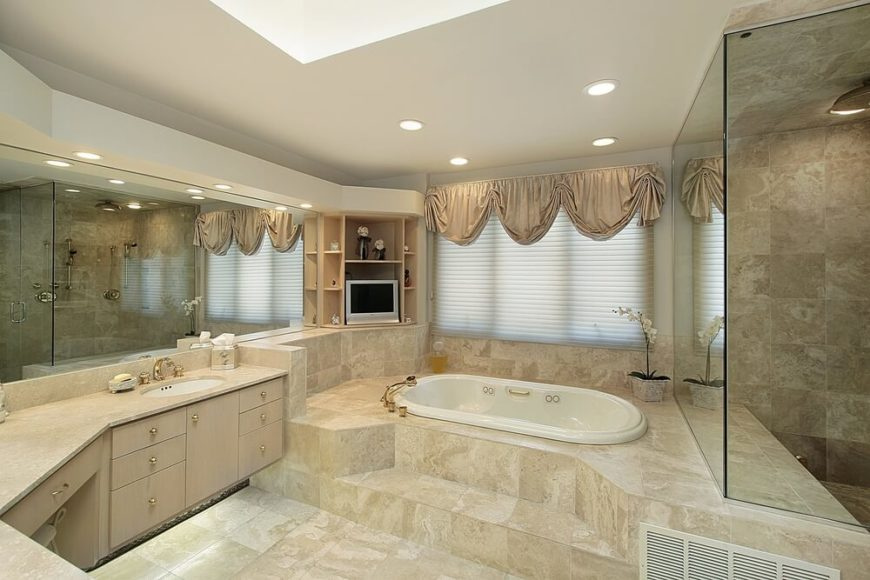 This upscale bathroom features extensive tile-work and subtly luxurious details. The recessed lighting, shaded window, and skylight work together in harmony to give this space a soft glow of natural light. Plenty of storage space is noted, and an enclosed shower area is just out of view.