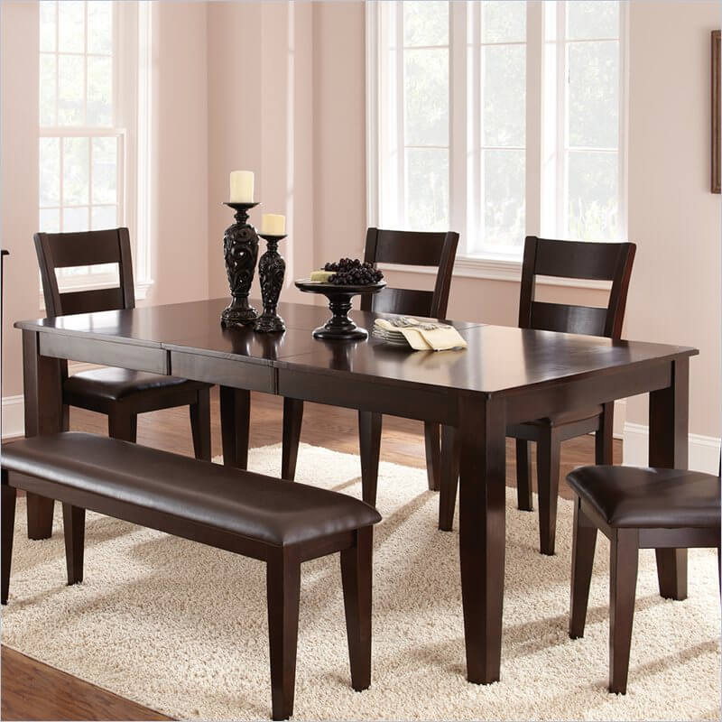 This contemporary dining table features tapered legs below a boxy, angular frame. Sleek expanse of surface hides a butterfly leaf.
