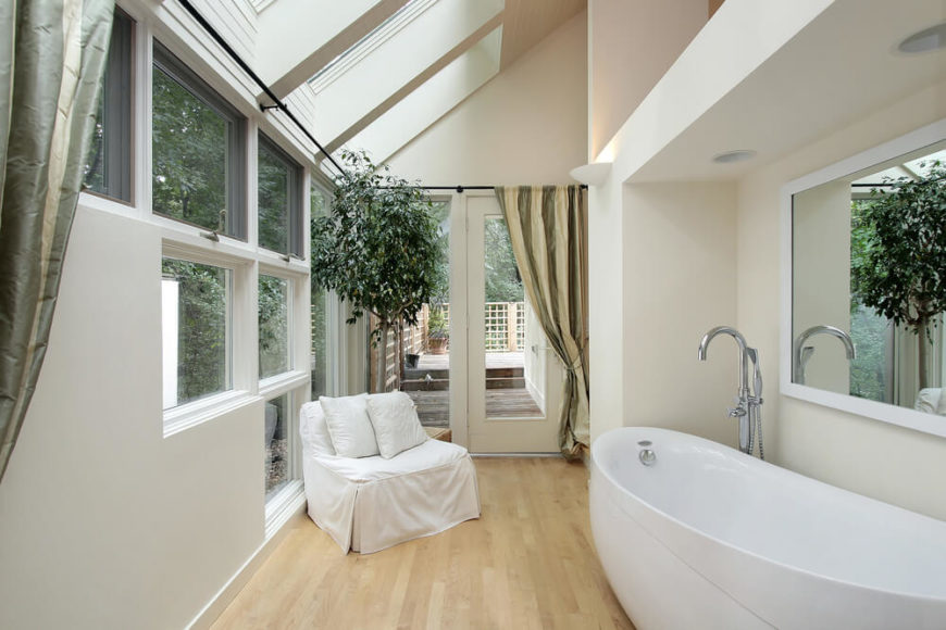Several skylights and unique window arrangements make this small bathroom space feel open and free. The light hardwood flooring complements the white modern bathtub and contrasts with the sage and olive drapery, while a view of a patio area can be seen through the door.