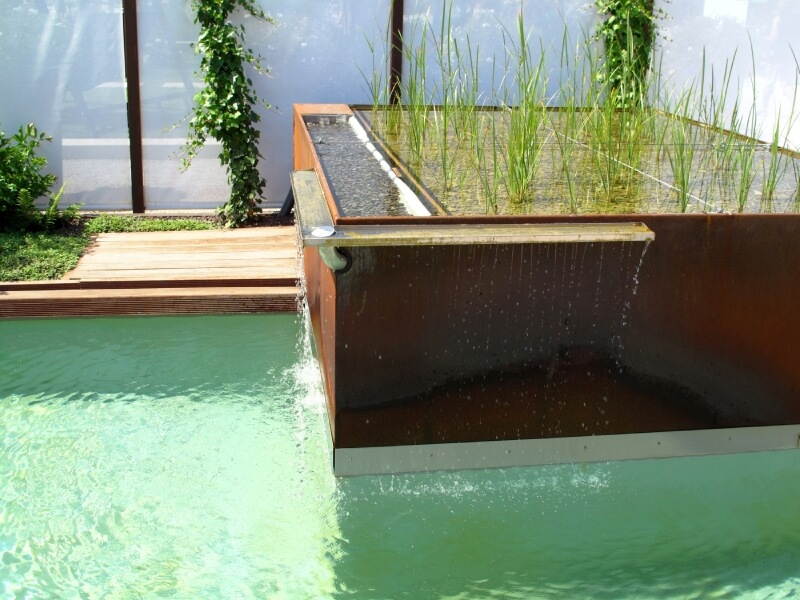 A modern take on the waterfall, a copper box with a small group of water-loving plants on the top and a small drainage gutter acting as a waterfall.