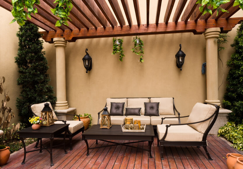 This beautiful covered deck is in a Spanish style, featuring hanging vines and sleek wooden furniture with a curved profile.
