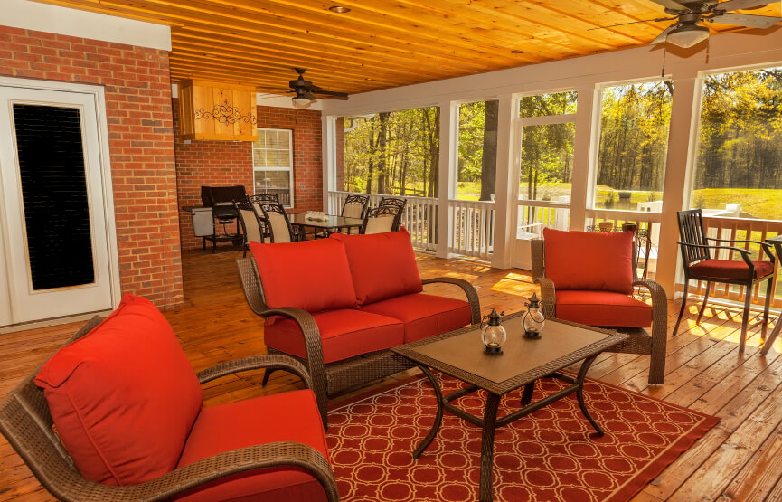 The bold red cushions and area rug pull the warmth out of the reddish wood decking and out of the home's brick facade. Chocolate-brown wicker furniture adds an air of the traditional.