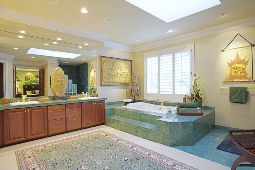 This India inspired bathroom boasts a gorgeous sea-green marbled bathtub casing, seen duplicated in the top of the gorgeous double vanity. A large coordinating area rug sits atop an ivory floor, while a skylight assists in brightening the space. Richly detailed decorations keep with the theme.