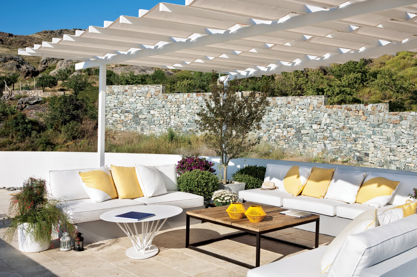 The pergola above this simple patio has a crinkled edge that adds a bit of visual interest to this white, modern setting.
