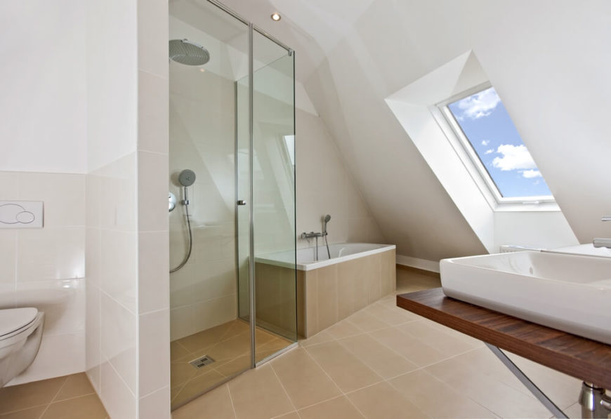 A modern bathroom features exquisite angles which add interest to this small space. A petite bathtub sits next to a small enclosed shower, while a glimpse of the daytime sky can be seen in the thoughtfully placed skylight.