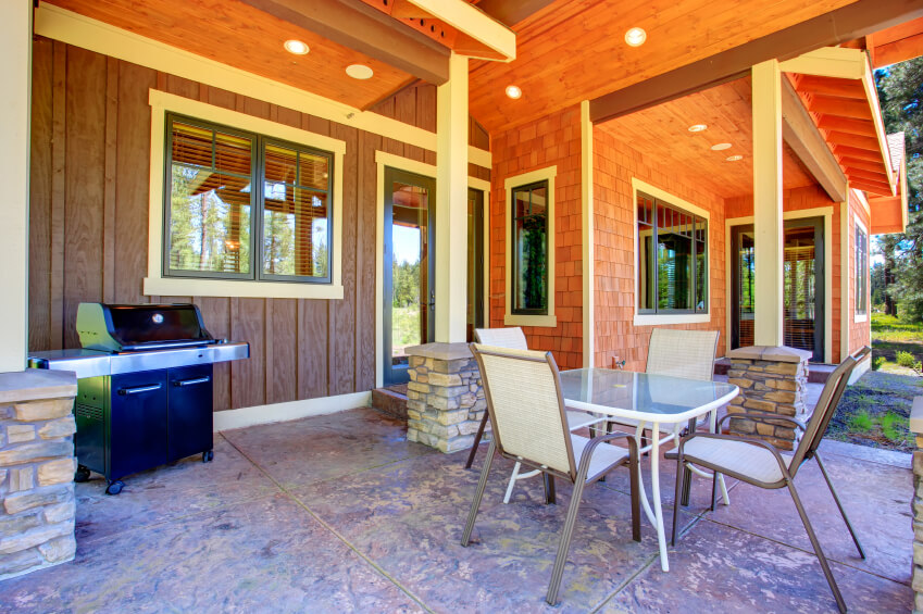 The mix of wooden siding with stone pillar supports and a mottled stone patio ensures that the eye never quite settles on any one part of this oddly-shaped pa