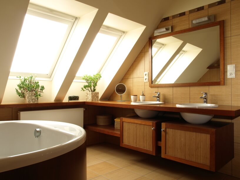 The double skylights featured above cast a comforting haze of light onto this exquisitely designed bathroom. Deep porcelain sinks are inset into a fine wood cabinet, and rest upon bamboo and wood storage cabinets beneath. A large mirror reflects the light gleaned from the skylights, maximizing the available natural light and further brightening the space.