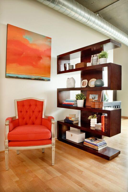 A open bookcase acts as a space separator and has an armchair that matches the chair in the living room.