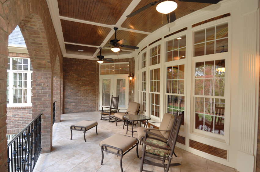This gorgeous covered terrace has a black wrought iron balustrade running between each brick arch. A symmetrical set of rocking chairs, patio chairs and ottomans against the bay windows provide elegance and style to this neutral relaxation area. A series of ceiling fans help keep air circulating on hot, still days.