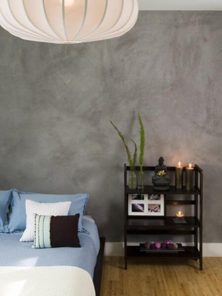 The upstairs bedroom has textured gray walls and a low-profile platform bed with blue and white bedding. A small three-tier shelf acts as a nightstand.
