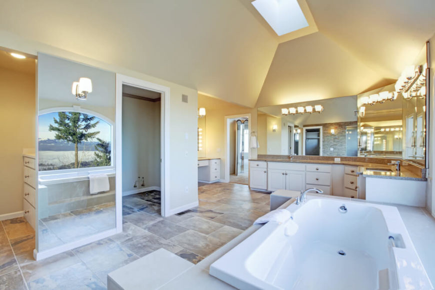 An absolutely breathtaking bathroom offers plenty of radiant light, soaring ceilings, and an arched picture window reflecting into a mirrored wall panel. The numerous mirrors and high ceilings contribute to the open, airy feel of this already sizable bathroom. A skylight shines down additional light, while large stone tiles offer interest and variation.