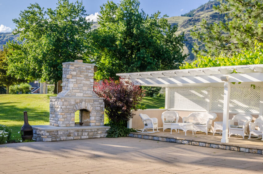 A pergola and trellis covers and encloses this simple raised stone patio filled with an abundance of white wicker patio furniture. To the left is a dual-sided stone wood-burning fireplace.