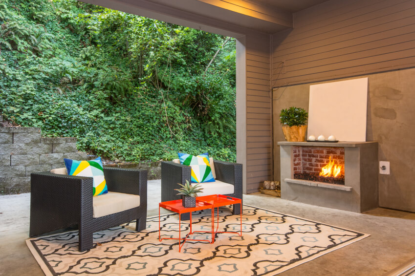 This cute contemporary covered patio is contained within what might have originally been an unused garage. The concrete patio is covered by a contemporary patterned rug in the seating area. A small concrete and brick fireplace projects heat into the seating area.