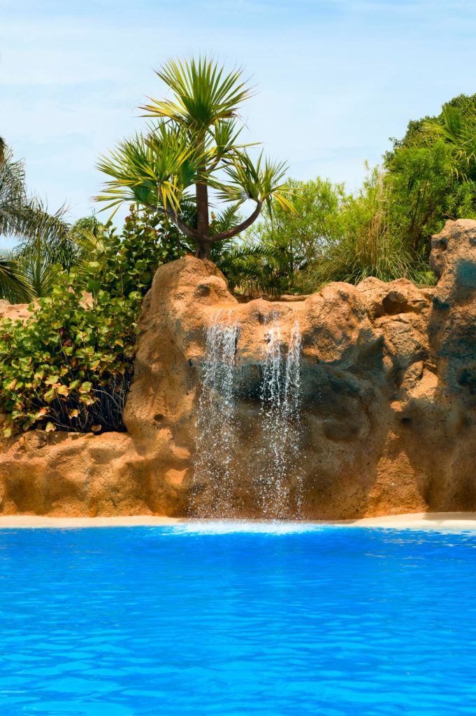 An artificial stone waterfall with a faux beach leading up to the edge.