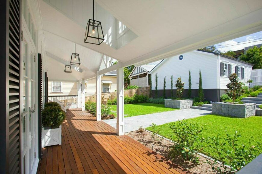 The spacious veranda of the home has windows that filter light onto the porch, gently warming the wood decking. Matching hanging light fixtures light the porch after the sun sets.