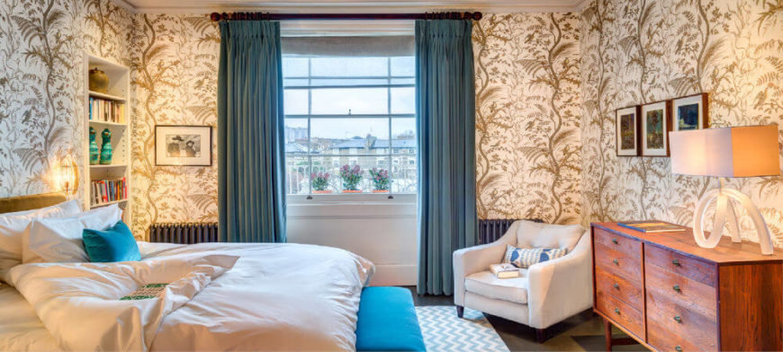 The primary bedroom suite has a bold foliage wallpaper in taupe and gold, and cozy white bedding with turquoise accents.
